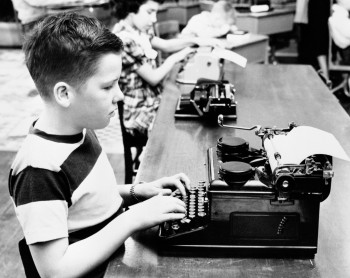 Boy and girl (6-7) using typewriters